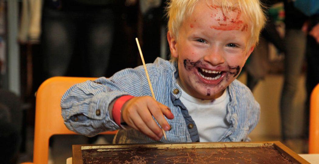 Blijde kindergezichten tijdens een workshop chocolade tekenen. Foto: Chocoa