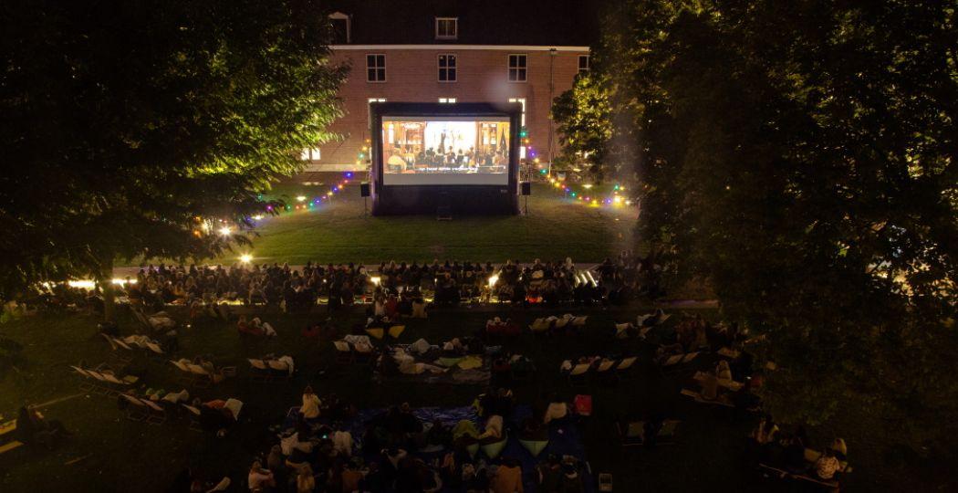 Lekker knus samen films kijken in de binnentuin van het Amsterdamse museum. Deze foto is van de vorige editie: dit jaar zorgt de organisatie voor genoeg afstand tussen bezoekers. Foto: Movies at the Hermitage, Vincent Capocchi.