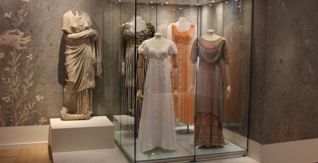 Prachtige jurken in Empirestijl; geïnspireerd op de damesmode van de Romeinen zoals het standbeeld naast de vitrine laat zien. Foto: Redactie DagjeWeg.NL