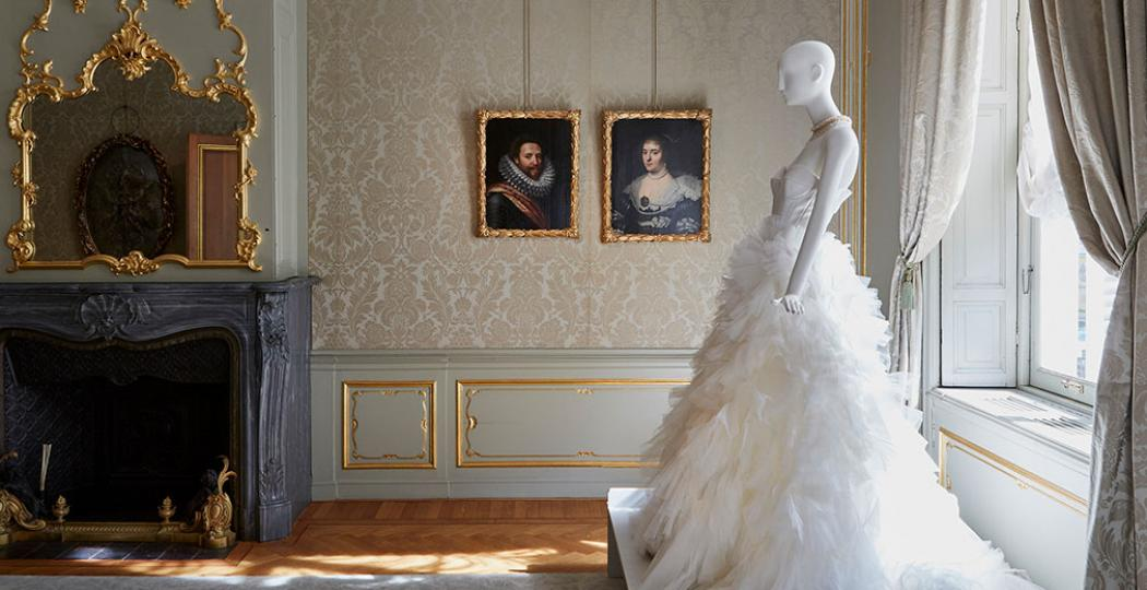 Een fraaie witte jurk naast de portretten die het ontwerp inspireerden. Foto: Nicole Marnati - locatie Hoogsteder Museum Stichting.