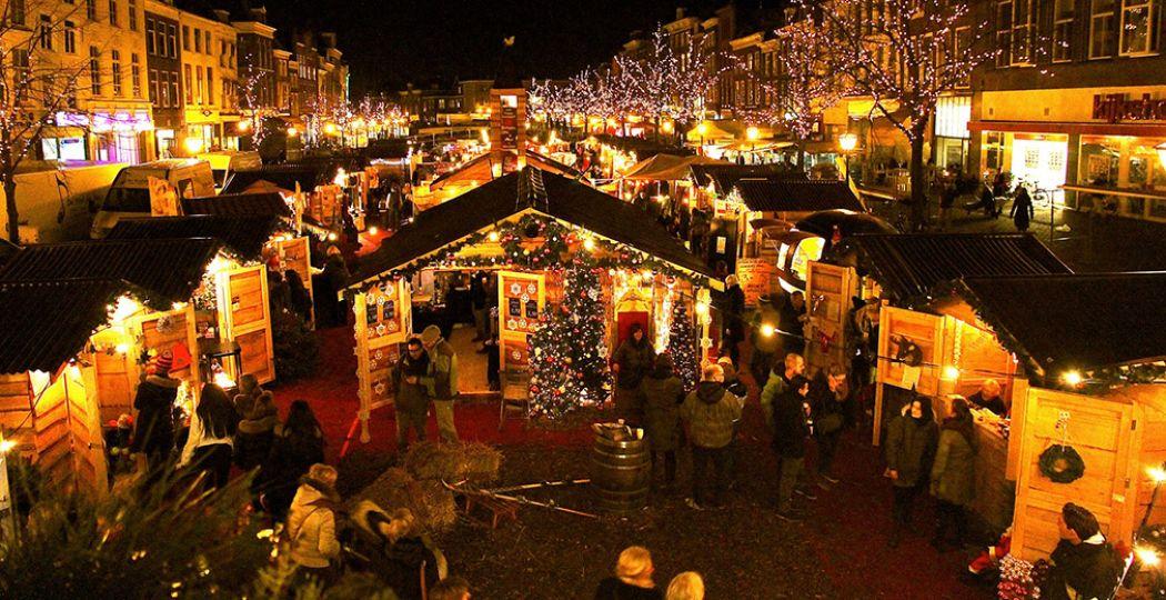 De drijvende kerstmarkt in Leiden. Lichtjes reflecteren in het water tussen de kerstchaletjes. Foto: Leiden Marketing