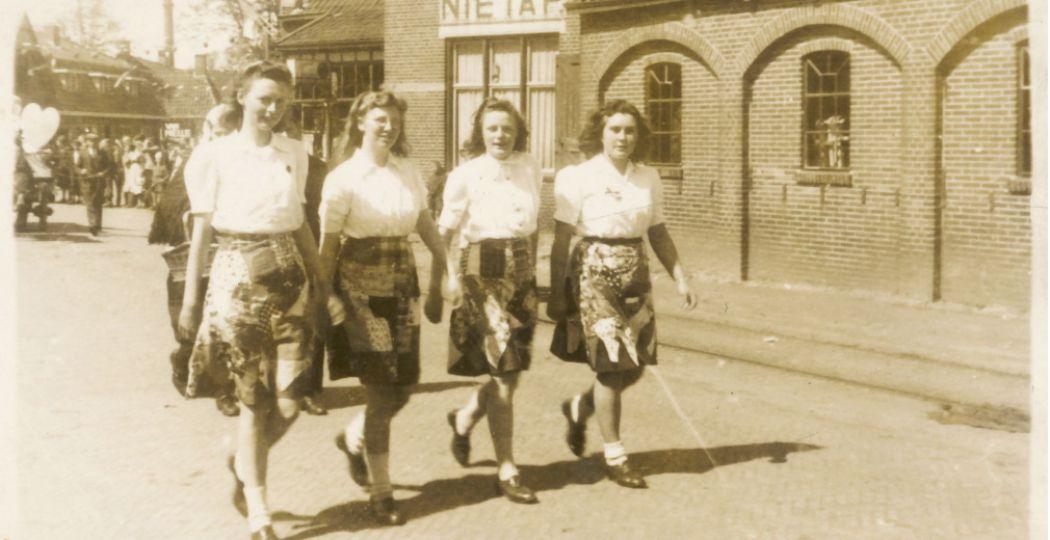 Vier meisjes (vlnr: Roelie v/d Velde, Lina Harms, Stien Bosman en lepie Buitenkamp) in hun Bevrijdingsrok, meelopend in de optocht ter gelegenheid van Koninginnedag 1946 in Leek-Nietap. Foto: Groninger Archieven.