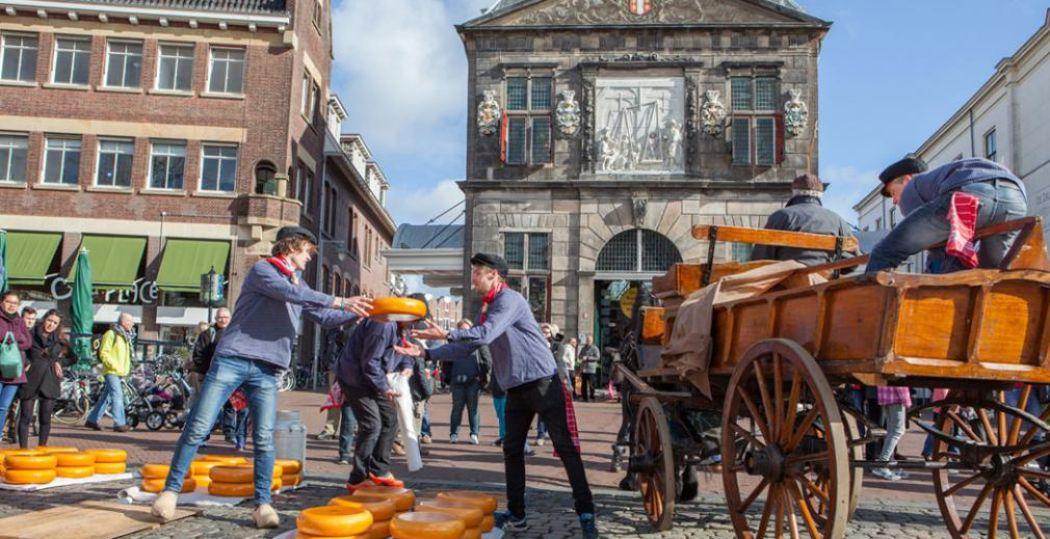 Op de Kaasmarkt voor de Waag gooien handelaren met kazen, een boeiend schouwsspel. Foto: VVV Gouda