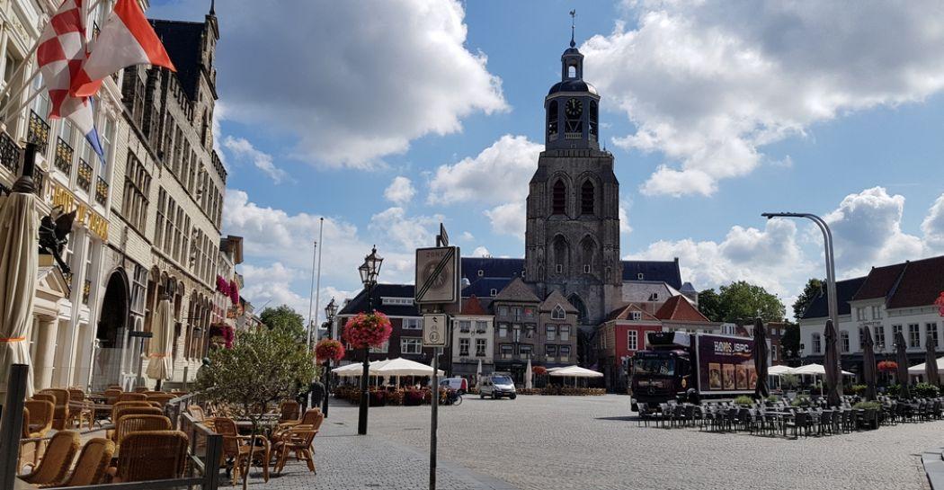 Een goed begin van een trip door Bergen op Zoom: de Grote Markt met overal terrasjes. Op de achtergrond de Sint Gertrudiskerk met toren De Pepermolen. Foto: DagjeWeg.NL / Tonny van Oosten