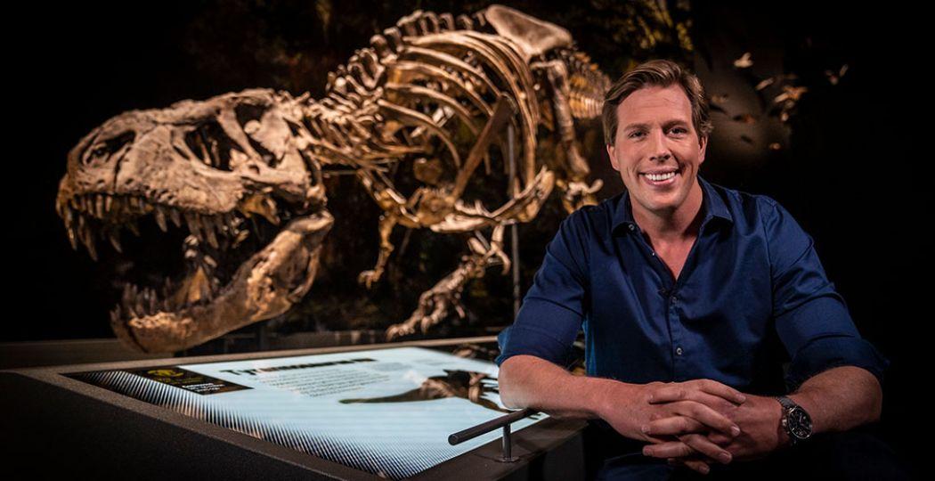 Freek Vonk bij Trixie, een van de beroemdste dinoskeletten ter wereld. Vonk vertelt je enthousiast waarom en nog veel meer tijdens je virtuele tour door Naturalis. Foto: Naturalis © Ivo Borkus