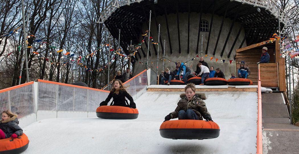 Roetsj van de grote sleebaan naast de molen! Het Nederlands Openluchtmuseum is een winterparadijs voor kinderen. Foto: Nederlands Openluchtmuseum.