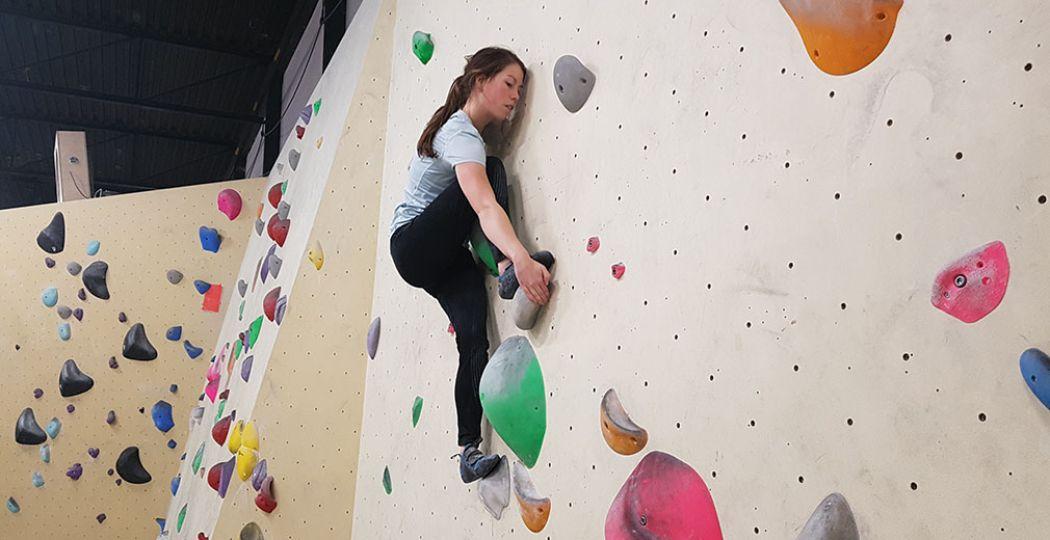 Nikki klimt geconcentreerd omhoog. Boulderen is een sport waarbij je je hele lijf traint. Het is ook een sociale sport en erg leuk om met een groep te doen. Foto: DagjeWeg.NL/Toli