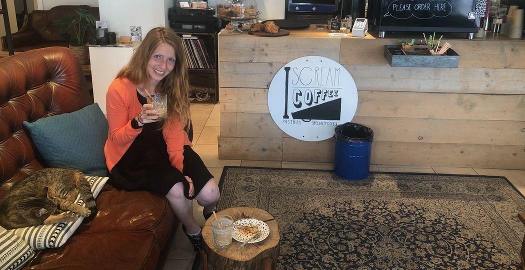 Willeke in haar favoriete koffiebar 'I Scream Coffee', waar ze niet alleen komt voor de lekkere koffie, maar ook voor het heerlijke vegan gebak. Buurtkat Knoopje is er ook. Foto: Laurent Legrand