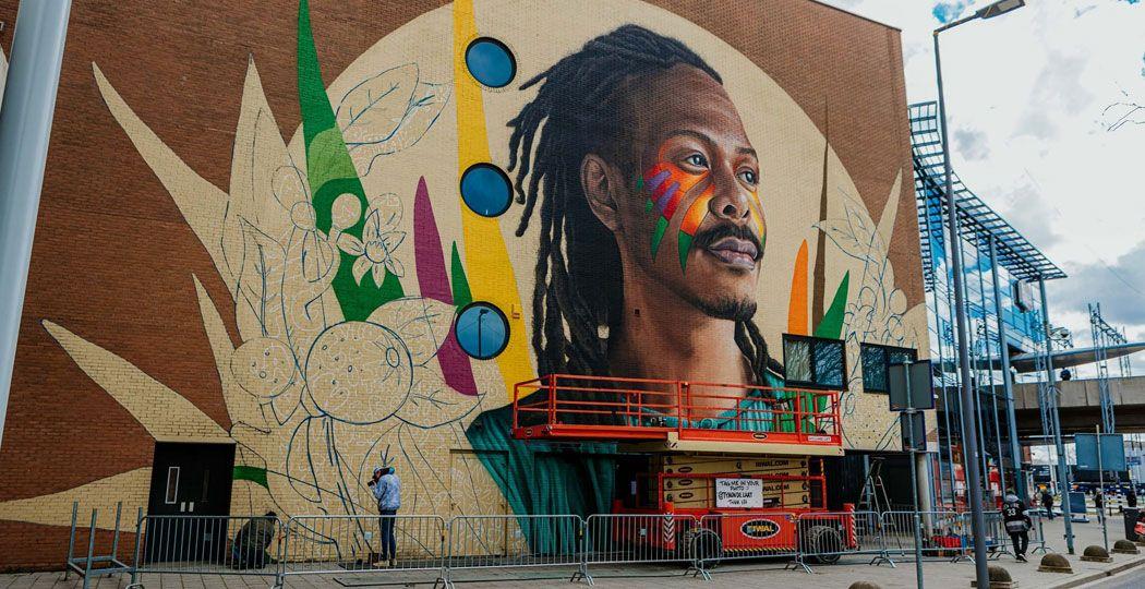 Kunstenaar Tymon de Laat creëerde een imposante muurschildering van Jeangu Macrooy tegenover Rotterdam Ahoy. Foto: Hiphop In Je Smoel © Rosa Quist