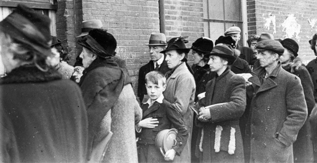 Tijdens de hongerwinter wachten inwoners voor de ingang van een schoolgebouw op hun beurt bij een voedseluitdeling van het ikb den haag 1944-45. Foto: Menno Huizinga, Nederlands Fotomuseum