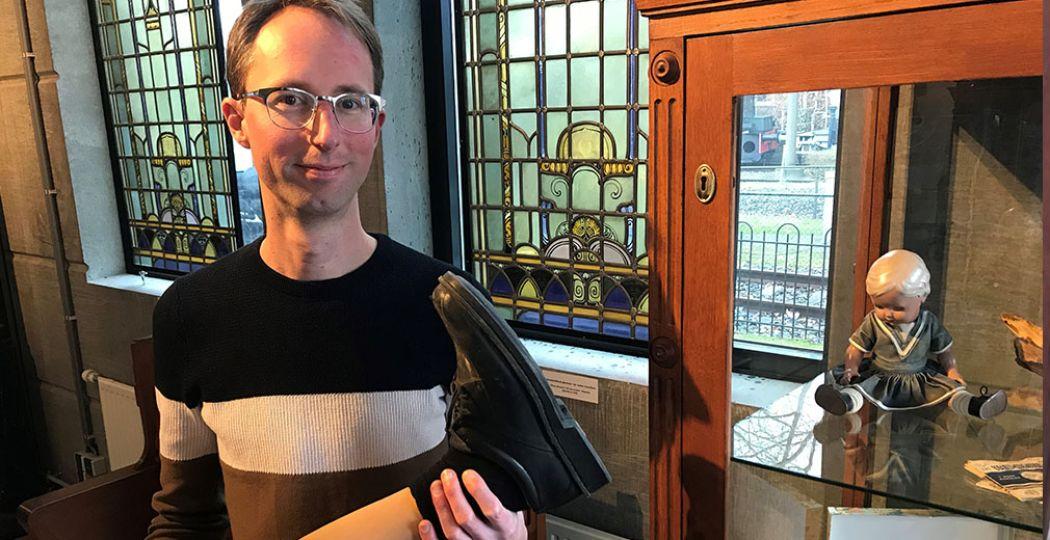 De conservator van Het Spoorwegmuseum, Tuur Verdonck, bij de vitrinekast vol bijzondere gevonden voorwerpen. Het kunstbeen paste er niet meer in. Foto: Het Spoorwegmuseum