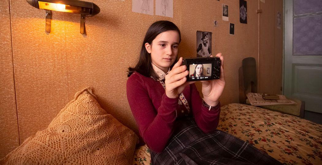 Anne Frank (gespeeld door de dertienjarige Luna Cruz Perez) in het Achterhuis met haar camera. Je kunt haar vlogs zien in de YouTube serie Anne Frank videodagboek. Foto: copyright Anne Frank Huis, fotograaf Ray van der Bas